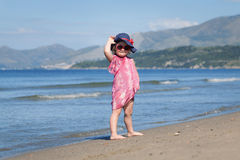 Happy girl in hat and sunglasses, walking near sea Stock Images