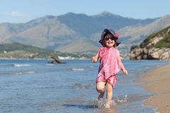 Happy girl in hat and sunglasses, walking near sea Royalty Free Stock Images