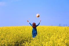 Girl walking in a field of yellow rapeseed royalty free stock image