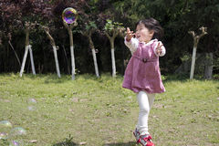 Happy girl have fun on eadow with soap bubbles toy Stock Images