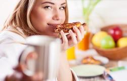 Happy girl having breakfast Stock Photos