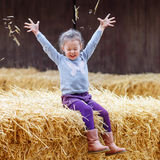 Happy girl having fun with hay on a farm Stock Photo