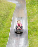 Happy girl having fun at summer bobsled track Royalty Free Stock Photography