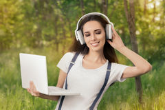 Happy Girl with Headphones and Laptop Listening to Music royalty free stock photo