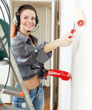 Happy  girl in headphones paints wall Royalty Free Stock Image