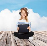 Happy girl with headphones showing tablet pc Stock Images