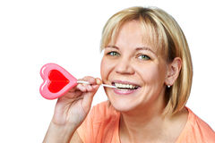 Happy girl with heart shaped lollipop Stock Photography