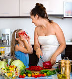Happy girl helping mother to cook Stock Image