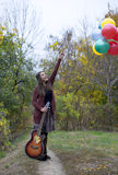 Happy girl with her balloons and guitar. In autumn royalty free stock photo