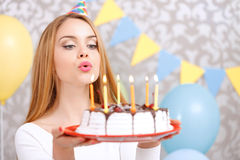 Happy girl and her birthday cake. Portrait of a young beautiful blond girl wearing cone cap holding a red plate with birthday cake and blowing candles making a Stock Photography