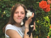 Happy young Girl and her kitty in hand stock photography