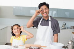 Happy girl with her father holding cookie molds in kitchen Stock Images