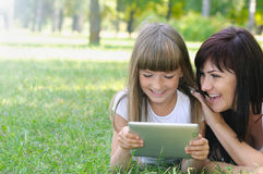 Happy girl and her mother having fun on the grass in the park Stock Photography