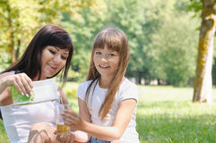 Happy girl and her mother having fun on picnic in the sunny summ Royalty Free Stock Photography