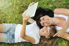 Happy girl and her mother having fun and taking selfie on the gr royalty free stock images