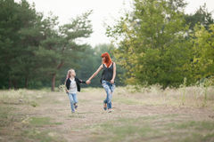 Happy girl with her mother hold hands and run along forest road. Happy girl with her mother laughing fun, hold hands and run along forest road on walk Royalty Free Stock Photography