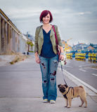 Happy girl with her pet. Pug standing on the pier Royalty Free Stock Photos