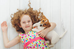Happy girl with her puppy Jack russell terrier lying on a wooden Royalty Free Stock Photo