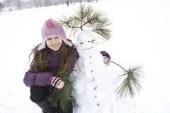 Happy girl with her snowman Stock Photos
