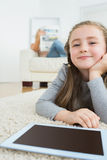 Happy girl with her tablet pc and her mother reading newspaper Royalty Free Stock Photography