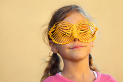Happy girl hides face behind butterfly mask Stock Image