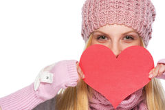 Happy girl hiding behind heart shaped valentines postcard. Happy girl in winter clothes hiding behind heart shaped valentines postcard Stock Image