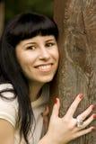 Happy girl hiding behind a tree. Closeup portrait of young happy attractive girl hiding behind a tree Royalty Free Stock Photo