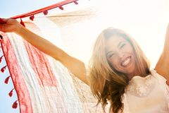 Happy girl hiding from sunlight under scarf. Royalty Free Stock Photo