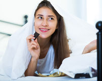 Happy girl hiding under sheet with sweets indoors Royalty Free Stock Photo
