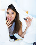 Happy girl hiding under sheet with sweets indoors Stock Photos