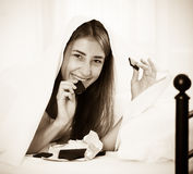 Happy girl hiding under sheet with sweets indoors Stock Images