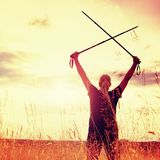 Happy girl  hiker with crossed poles in evening golden meadow Royalty Free Stock Image