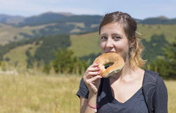 Happy girl hiker eating a doughnut outdoors Stock Photography