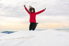 Happy girl jumping on snow covered mountain top. Happy girl hiker jumping on snow covered mountain top Royalty Free Stock Image