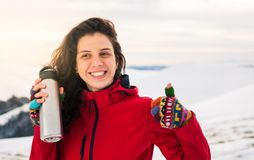 Happy girl with thermos on snowy mountain royalty free stock images