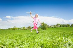 Happy girl holding airplane toy in green meadow Stock Photos
