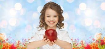 Happy girl holding apple over garden background stock photo