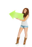 Happy girl holding an arrow pointing left Royalty Free Stock Images