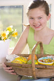 Happy girl holding basket of wooden Easter eggs Royalty Free Stock Photo