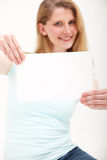 Happy girl holding blank paper at arms length Royalty Free Stock Images