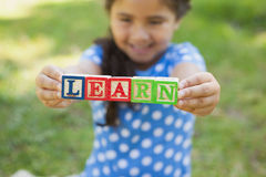 Happy girl holding block alphabets as 'learn' at park Royalty Free Stock Photo