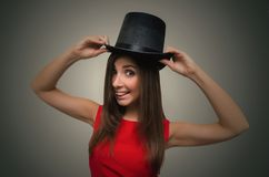 Woman with bowler hat. Happy girl is holding a bowler hat above her head . The magician woman stock images