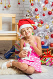 Happy girl holding a candle in his hand and sitting at the Christmas trees Stock Photos