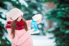 Happy girl holding Christmas candlelight outdoors on beautiful winter snow day Stock Photos