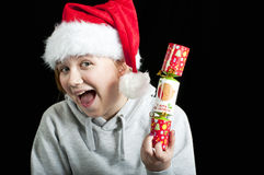 Happy girl holding a christmas cracker Stock Photos
