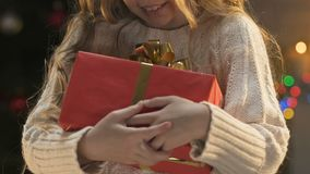 Happy girl holding Christmas gift, concept of orphanage volunteering at holidays. Stock footage stock video