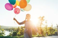 Happy girl holding colorful balloons in the city park, playing a. Front view of happy girl holding colorful balloons in the city park, playing, running against royalty free stock image