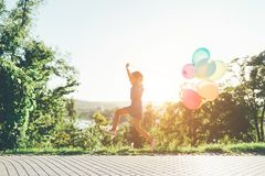 Cute girl holding colorful balloons in the city park, playing, r. Happy girl holding colorful balloons in the city park, playing, running, jumping against blue Stock Images