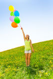 Happy girl holding colorful balloons in summer Royalty Free Stock Photography