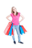 Happy girl holding colorful shopping bags and smiling. As spree and leisure concept isolated on white Stock Photos